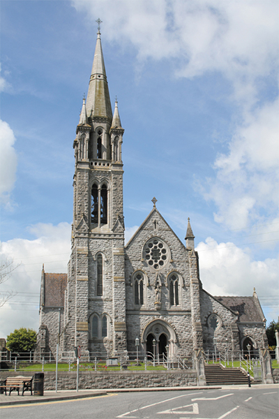 Figure 1: A photograph of the Gothic Revival church erected to a design by Maurice Alphonsus Hennessy (1848/9-1909) of Cork and Limerick. George Coppinger Ashlin (1837-1921) had been invited to submit a design, but declined, while drawings in the Royal Hibernian Academy show the unexecuted proposal by Walter Glynn Doolin (1850-1902) of Dublin. Begun in 1898, the church was dedicated in 1902 although the eye-catching steeple was completed only in 1908-9