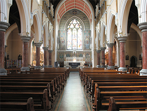 "Figure 2: A view of the interior looking towards the sanctuary with the impressive ""West Window"" supplied (1900) by John Hardman and Company (founded 1838) of Birmingham depicting The Exaltation of the Holy Cross.  The decorative mosaic work was completed (1919-21) under the aegis of Reverend Michael Madden PP.  The windows in the side chapels are signed by Mayer and Company (founded 1847) of Munich and London.  Click here to view of a photograph of the interior from the William Lawrence Collection (1880-1914)"
