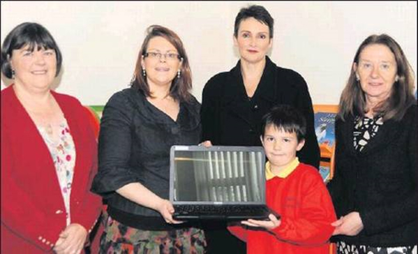 Noelle Foley, Marketing and Advertising Executive with the Corkman newspaper preseting the prize of a laptop for the school to Michael Cox, a pupil at St. Joseph's Infant School Charleville, who won the Hallowe'en Writing Competition in 2012.